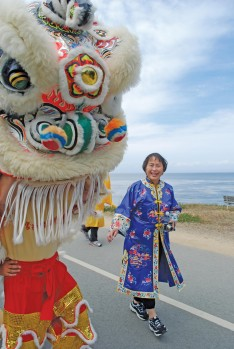 Gerry Low-Sabado and a lion dancer on the Rec Trail in the 2014 Walk of Remembrance